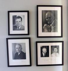 The study is adorned with presidential photos.